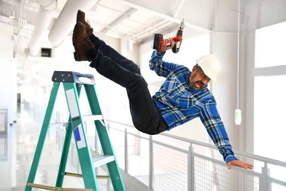 workplace hazards where man slips off ladder with a drill in his hand