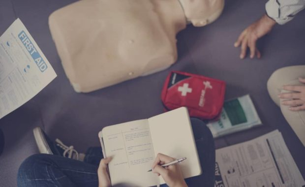 First aid level 1 training for employees with first aid notes and cpr dummy